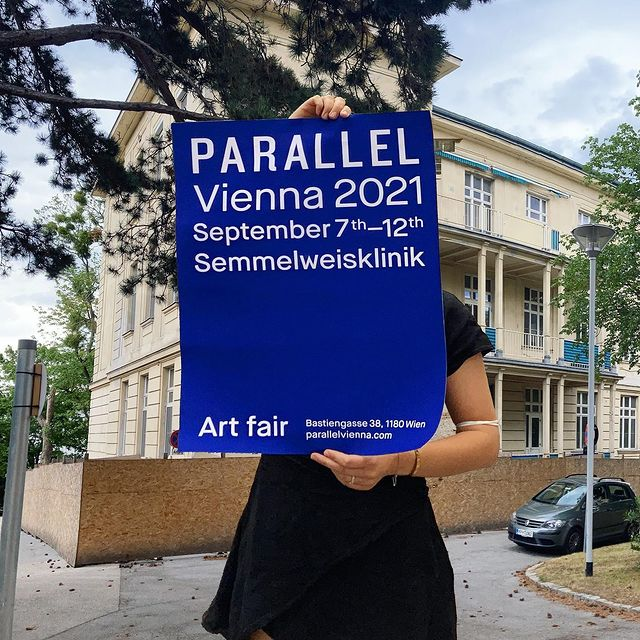 """News Hidéo Snes: A person holding a blue poster saying: """"Parallel Vienna 2021 September 7th-12th at Semmelweisklinik Vienna"""""""