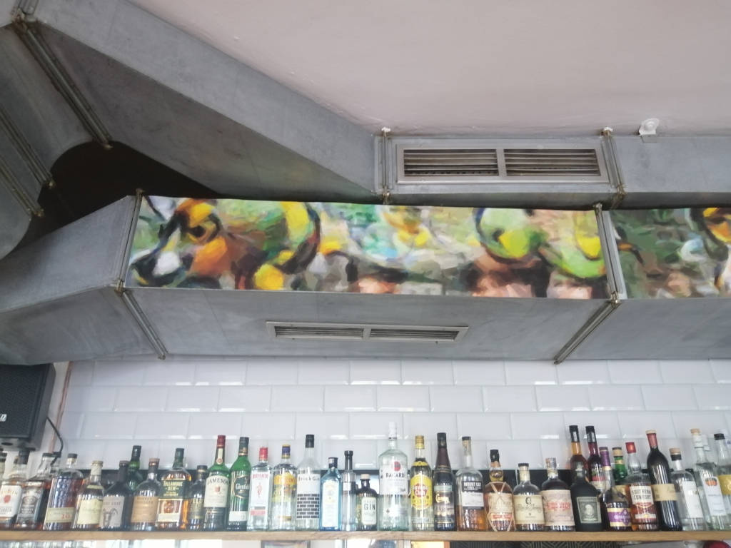 The Villa Vida Café is a Bar that belongs to the Rosa Lila Villa, a community space for LGBTQIA+ people. In this setting the colorful expanded paintings through an Artificial Intelligence are a permanent installation at the space and cover the large metal aircondition vents therein.