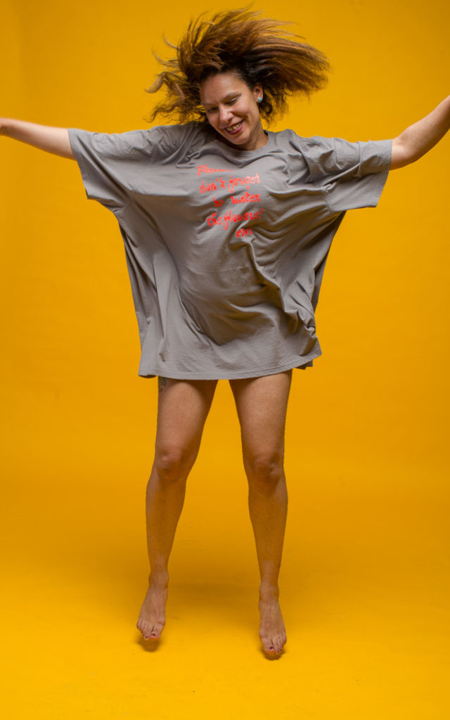 """A long, flowing, grey 5XL T-Shirt with a neon-orange print saying """"Please don't forget to water the flowers, Xoxo!"""", worn by a female model in front of a yellow background."""